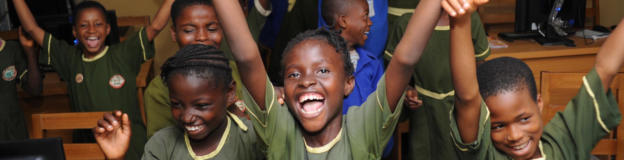 African children holding hands in classroom.