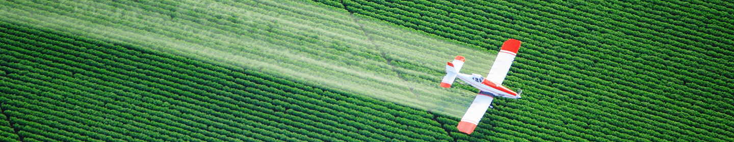 Aerial view of a crop duster flying over field.